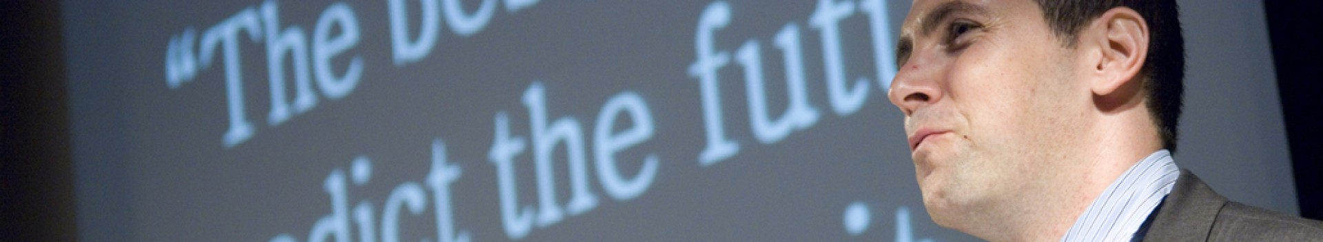 """Man by projector screen showing """"The best way to predict the future is to create it"""""""